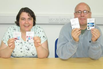 Female and male holding a card