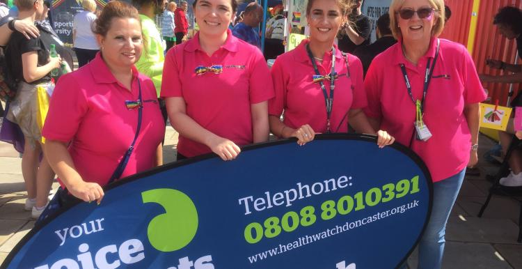 Four females stood in front of a banner that says Healthwatch Doncaster