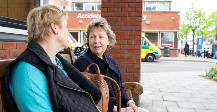 Two women sat down outside a hospital