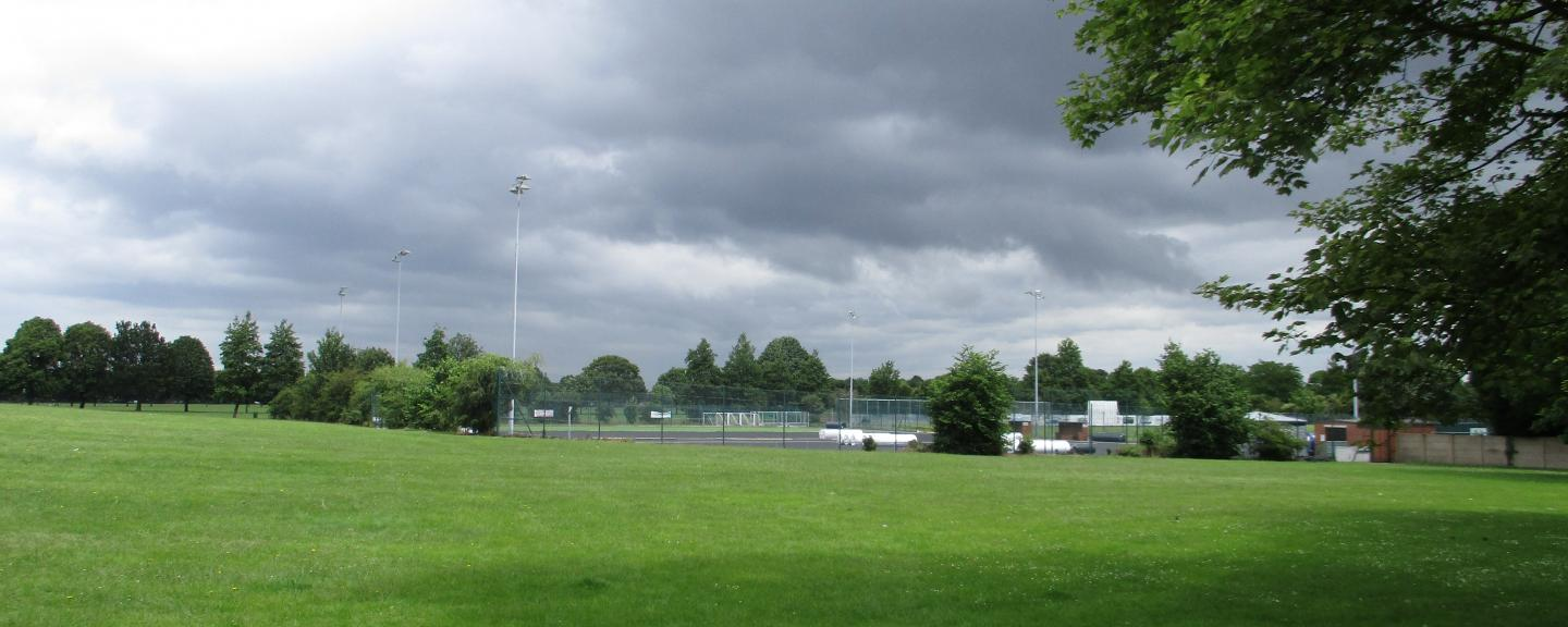 A field with a outdoor football area in the background