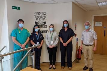 Five healthcare professionals stood up wearing a mask
