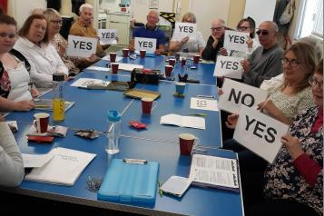 A group of volunteers sat around the table at a meeting holding up Yes or No signs