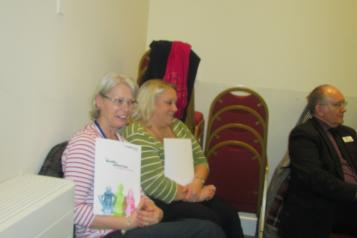 Two women sat down holding a brochure smiling at the camera
