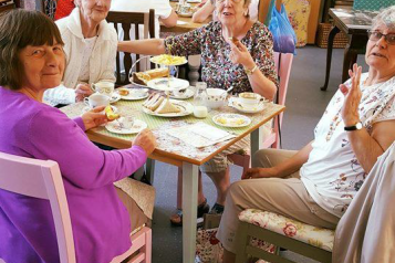 A group of older women sat around the table with cups of tea