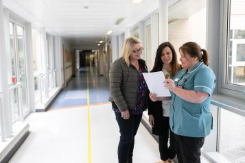Three women talking in hospital corridor