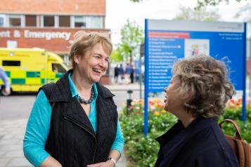 Two women speaking to one another outside a hospital