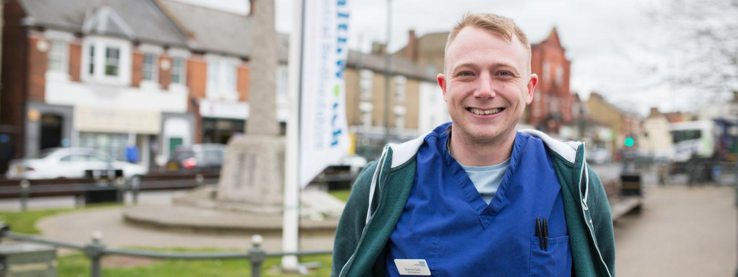 Man who works for the NHS standing outside at a Healthwatch community event