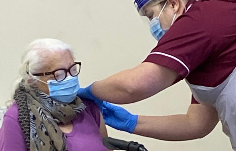 An elderly woman receiving an injection