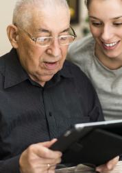 Woman helping an elderly man use a IPad