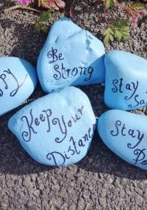 Blue coloured rocks with messages of positivity written on them